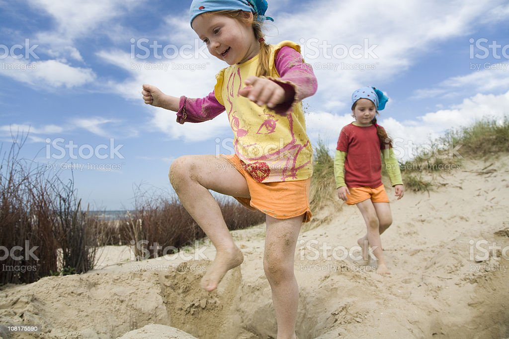 Two Little Girls playing in Sand Dunes on Beach royalty-free stock photo