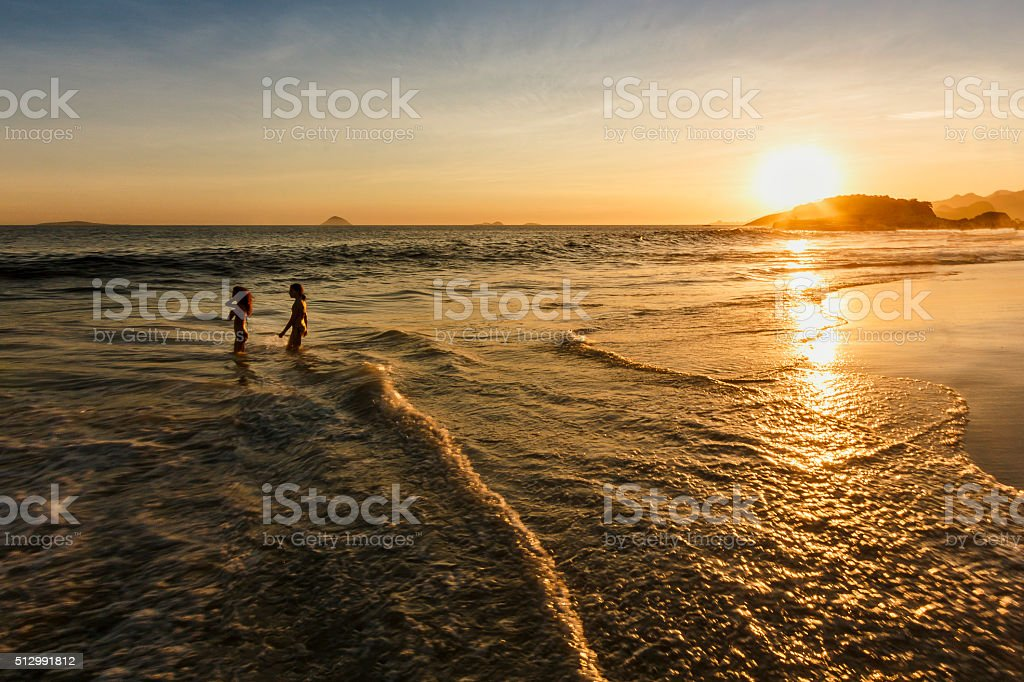 Two Little Girls Playing on Shallow Water on Empty Beach stock photo