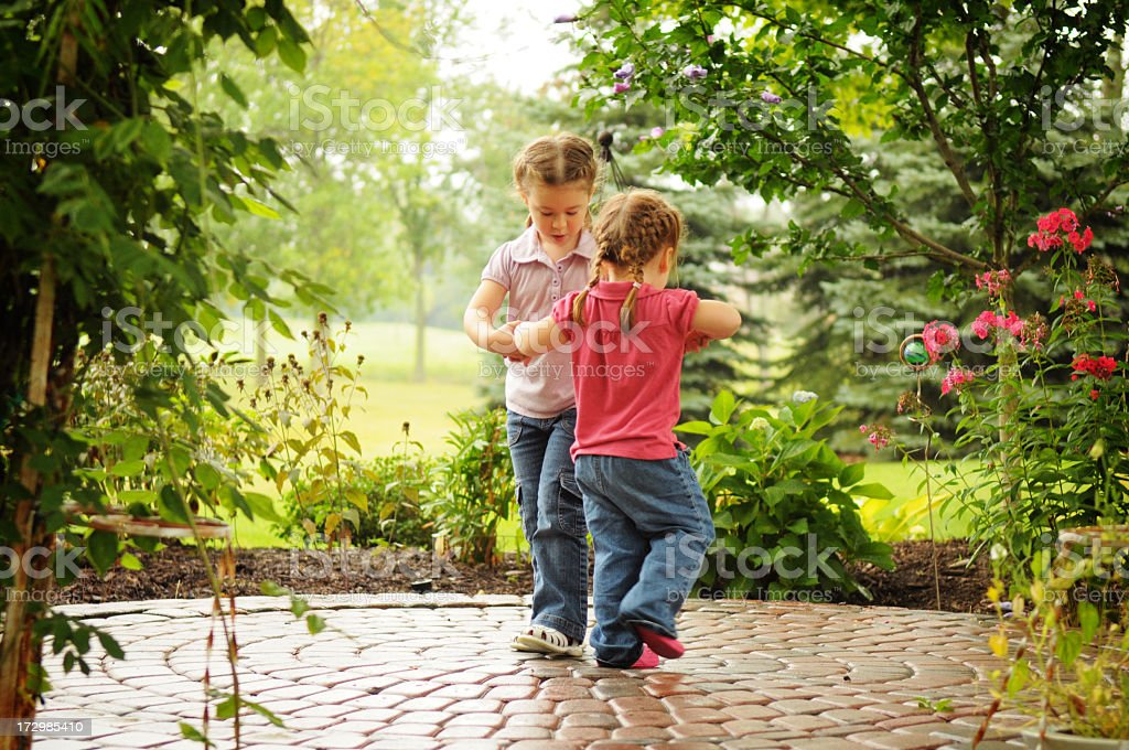 Two Little Girls Playing Ring Around the Rosy royalty-free stock photo