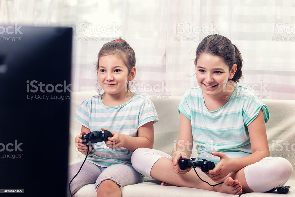 Two Little Girls Playing Video Games stock photo