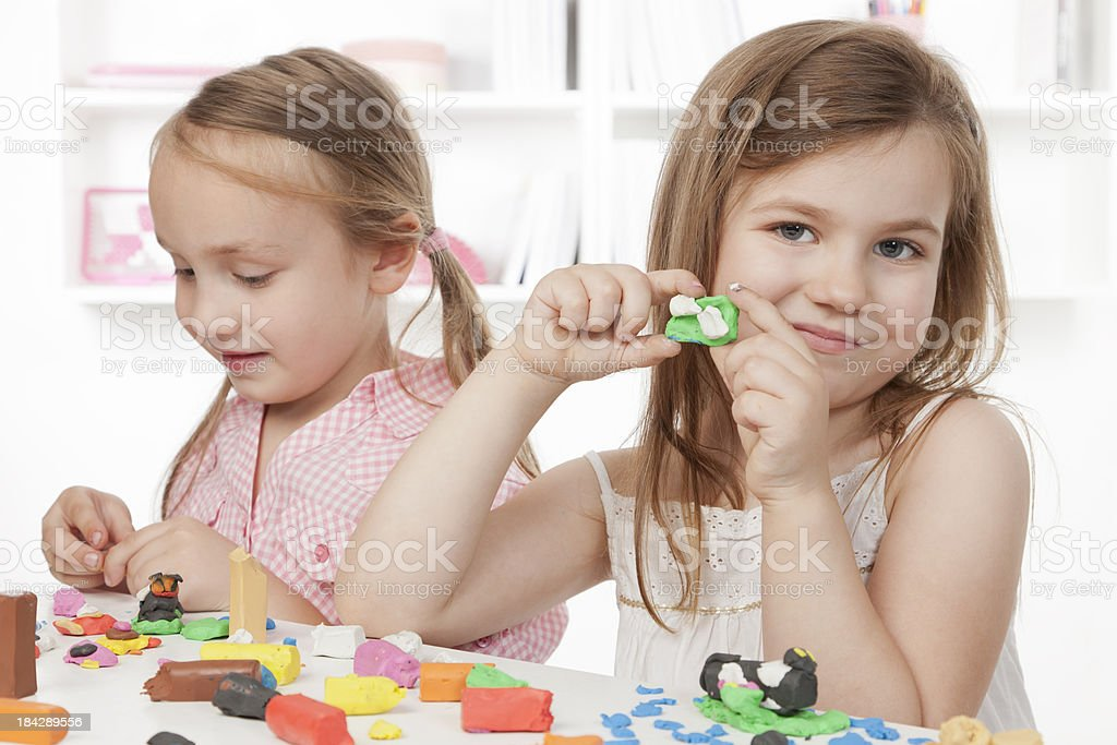 Two little girls playing with playdough royalty-free stock photo