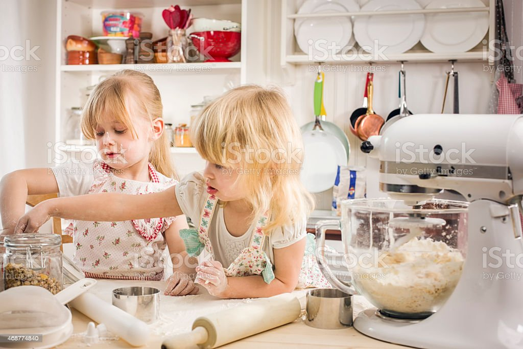 Two Little Girls Preparing Cookies in the Kitchen stock photo