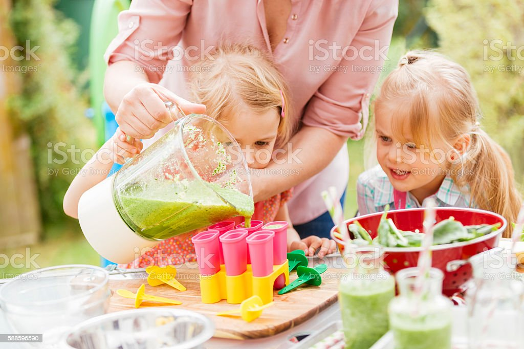 Two Little Girls Preparing Popsicles at Home stock photo