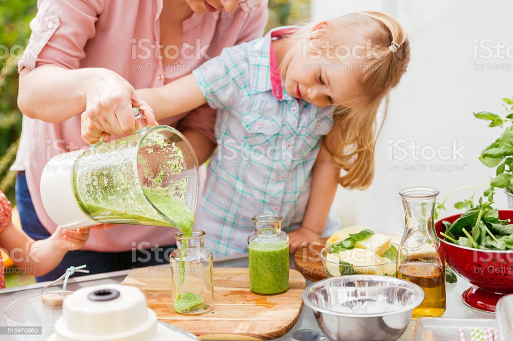 Two Little Girls Preparing Smoothies with Her Mother stock photo