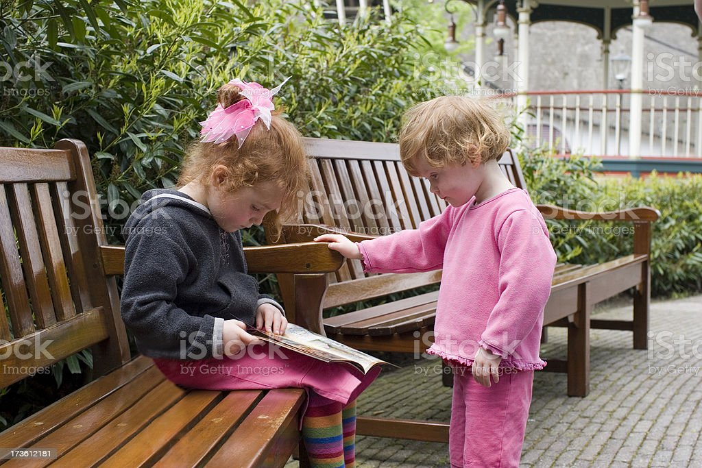 Two little girls reading in the park royalty-free stock photo