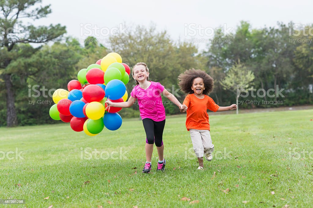 Two little girls running with bunch of balloons at park stock photo