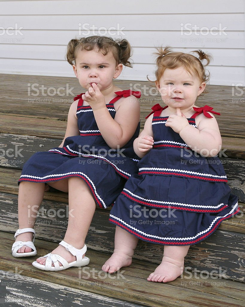 Two little girls sitting on a porch in sundresses royalty-free stock photo