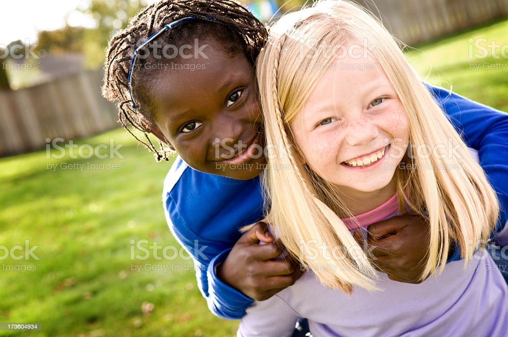 Two Little Girls Smiling and Riding Piggyback Outside royalty-free stock photo