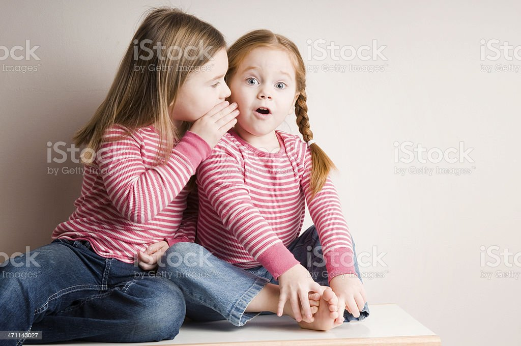 Two Little Girls Whispering Surprising Secrets stock photo