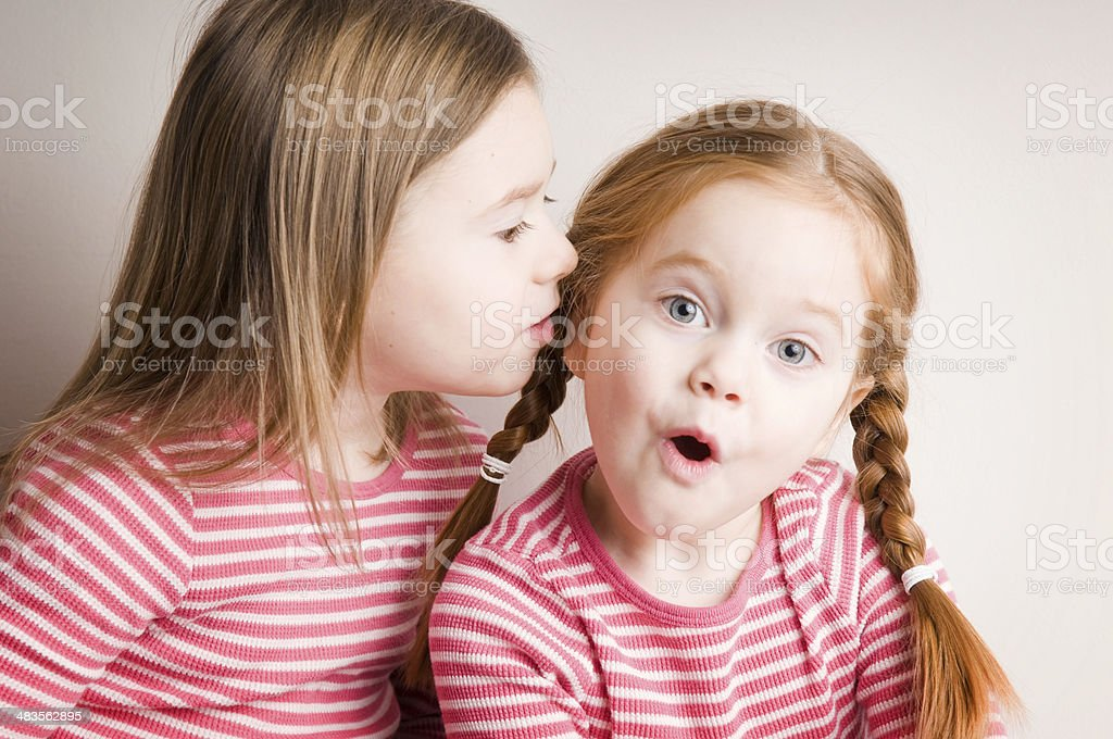 Two Little Girls Whispering Surprising Secrets royalty-free stock photo