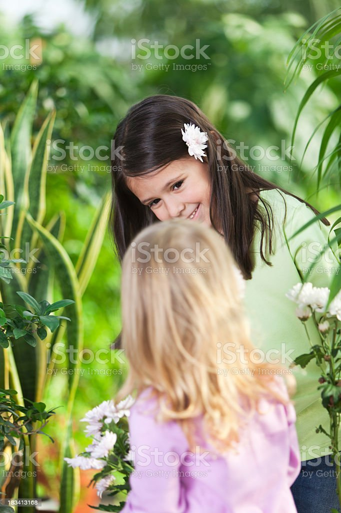 Two little girls with spring flowers stock photo