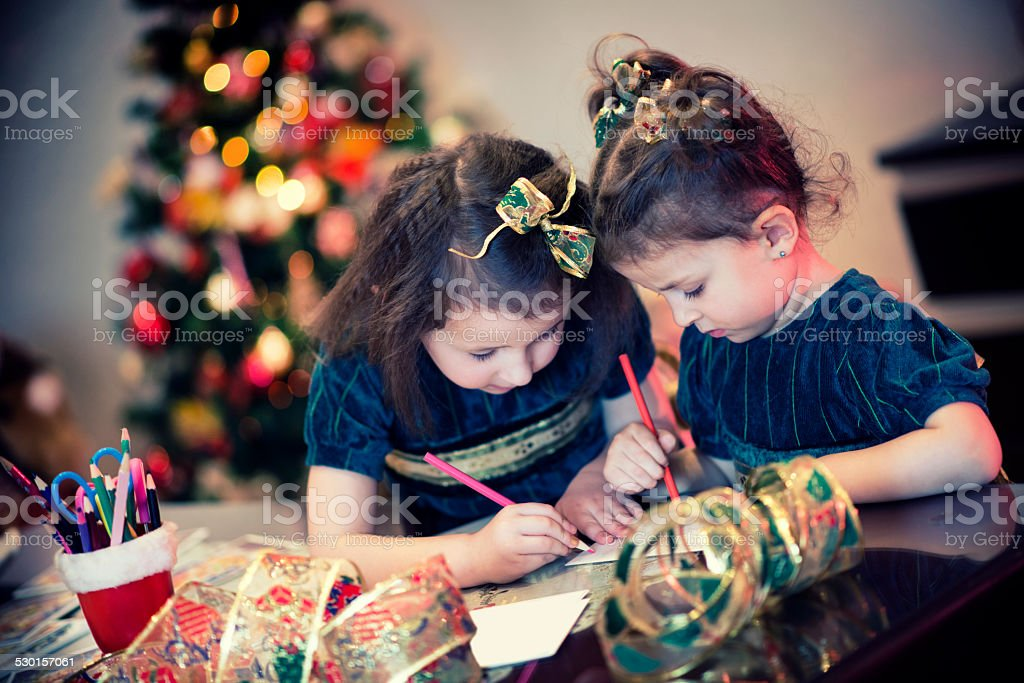 Two Little Girls Writing Their Wishes on Letter to Santa stock photo
