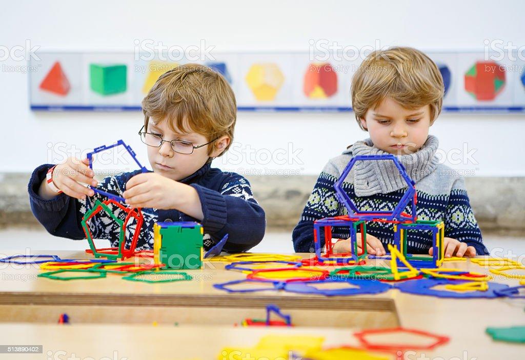 Two little kid boys building geometric figures stock photo