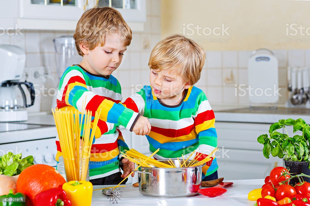Two little kid boys cooking pasta with vegetables stock photo