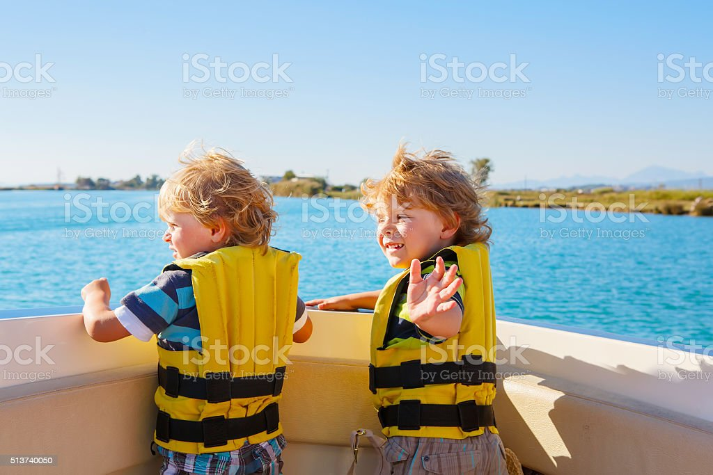 two little kid boys enjoying sailing boat trip stock photo