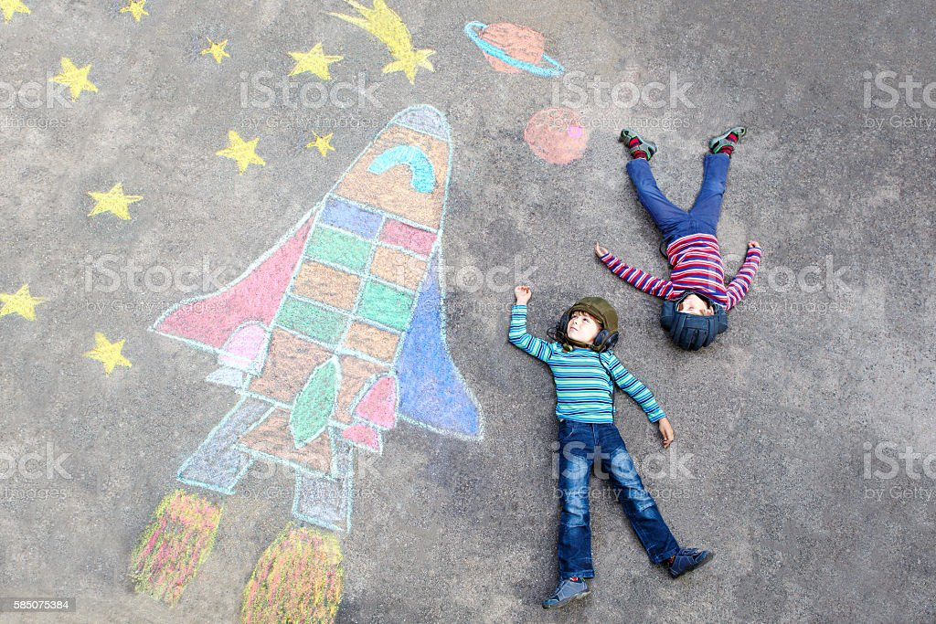 Two little kid boys flying by space shuttle chalks picture stock photo