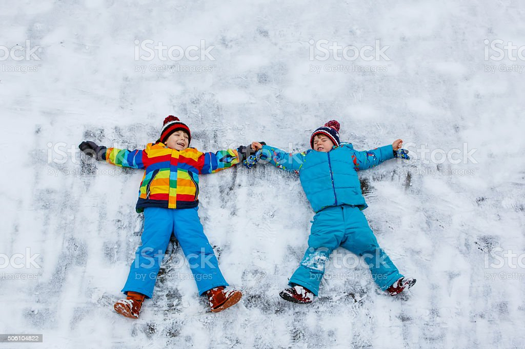 Two little kid boys making snow angel in winter, outdoors stock photo