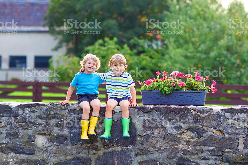 Two little kid boys sitting together on stone bridge stock photo
