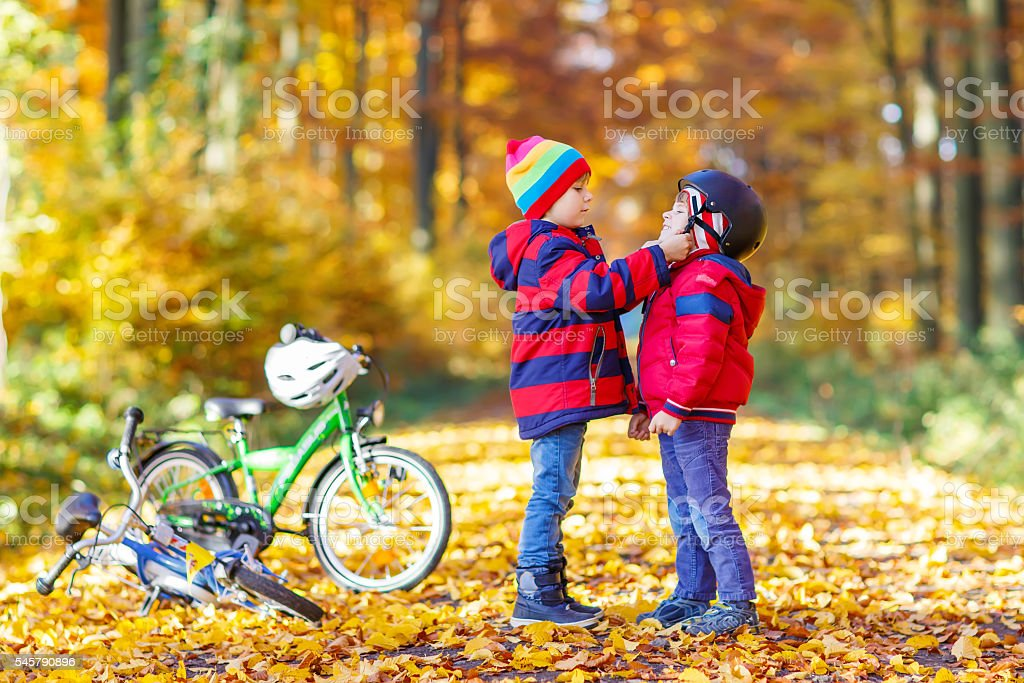 Two little kid boys with bicycles in autumn park stock photo
