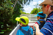 Two little kids boys and father making Everglades boat tour