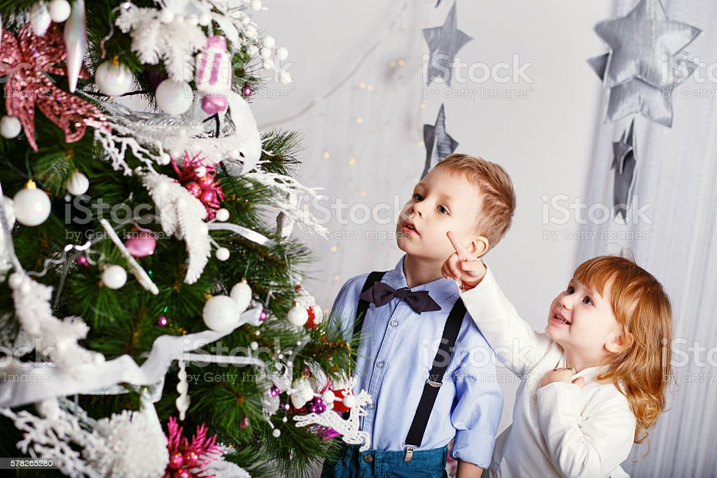 Two little kids decorating Christmas tree with toys, flowers and stock photo