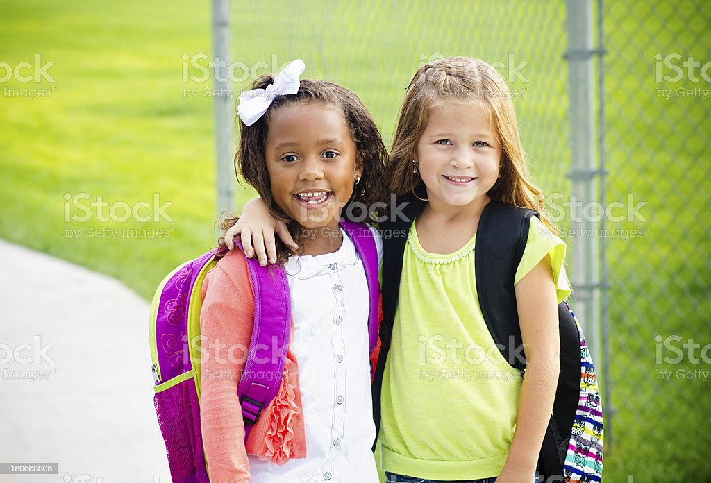 Two little kids going to school together stock photo
