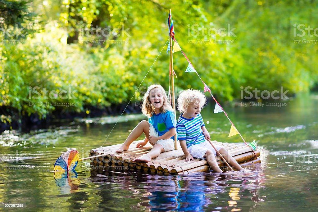 Two little kids on wooden raft stock photo