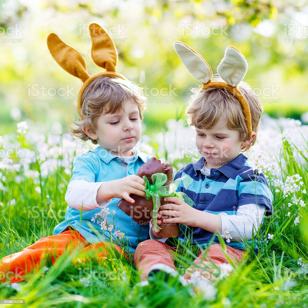 Two little kids playing with Easter chocolate bunny outdoors stock photo