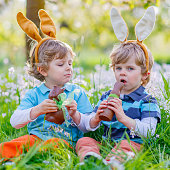 Two little kids playing with Easter chocolate bunny