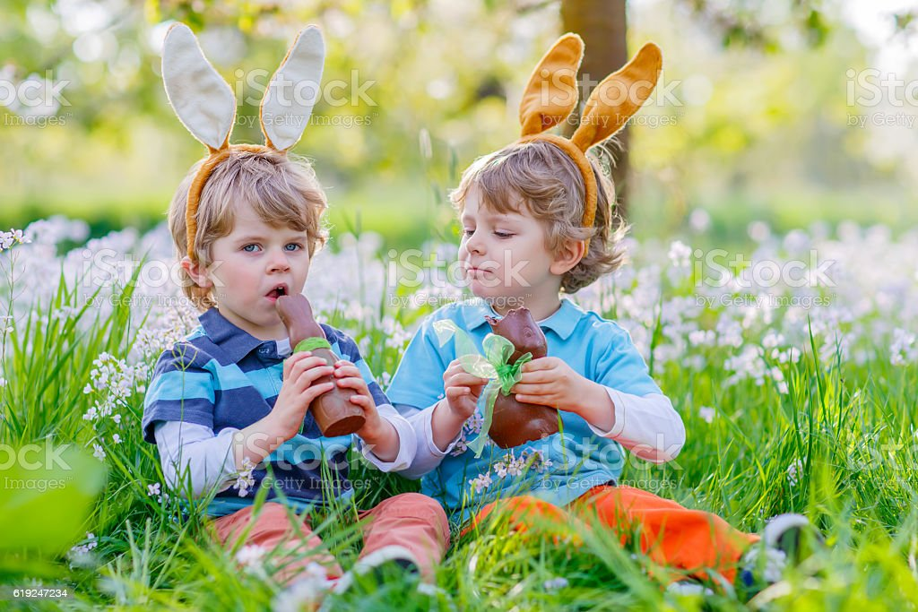 Two little kids playing with Easter chocolate bunny stock photo