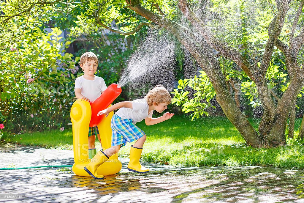 Two little kids playing with garden hose and water stock photo