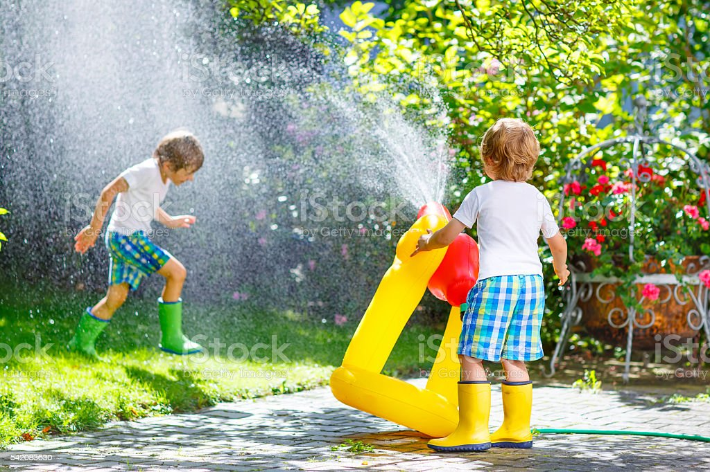 Two little kids playing with garden hose in summer stock photo