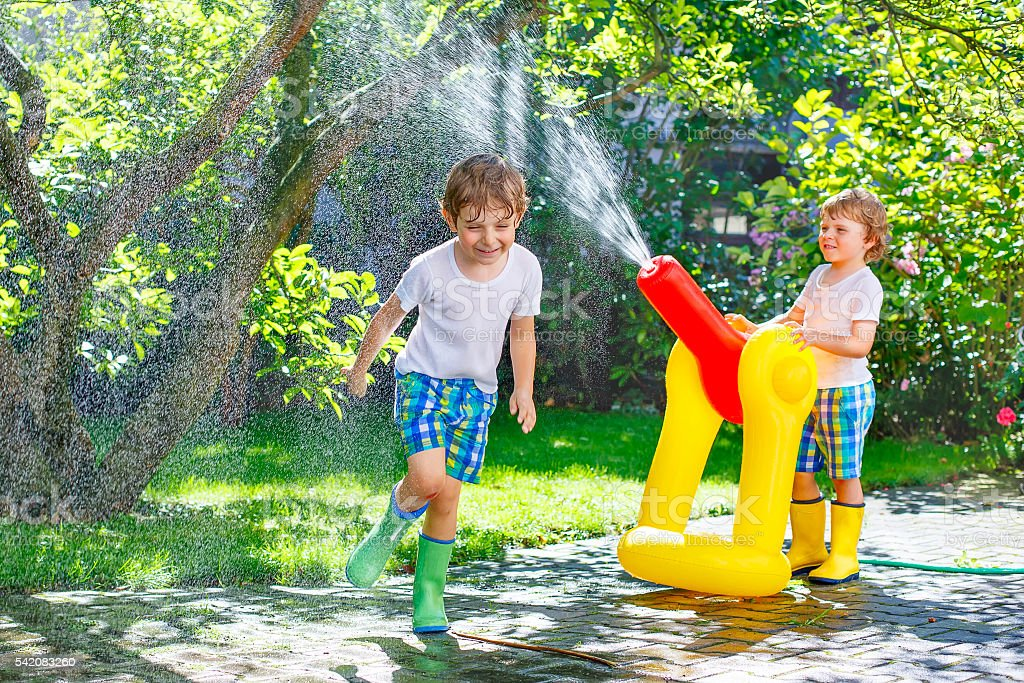 Two little kids playing with sprinkler and water in summer stock photo