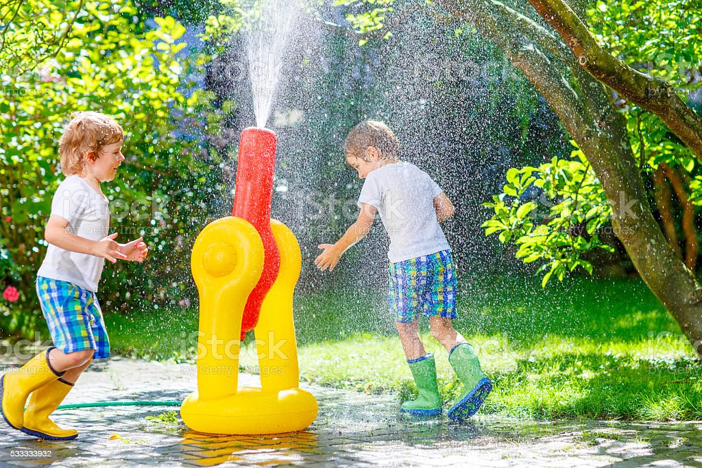 Two little kids playing with water sprinkler stock photo