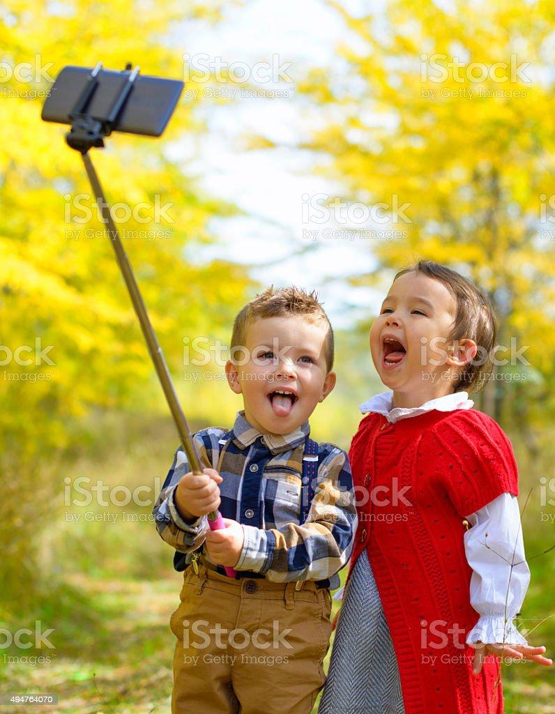 Two little kids taking selfie in park stock photo