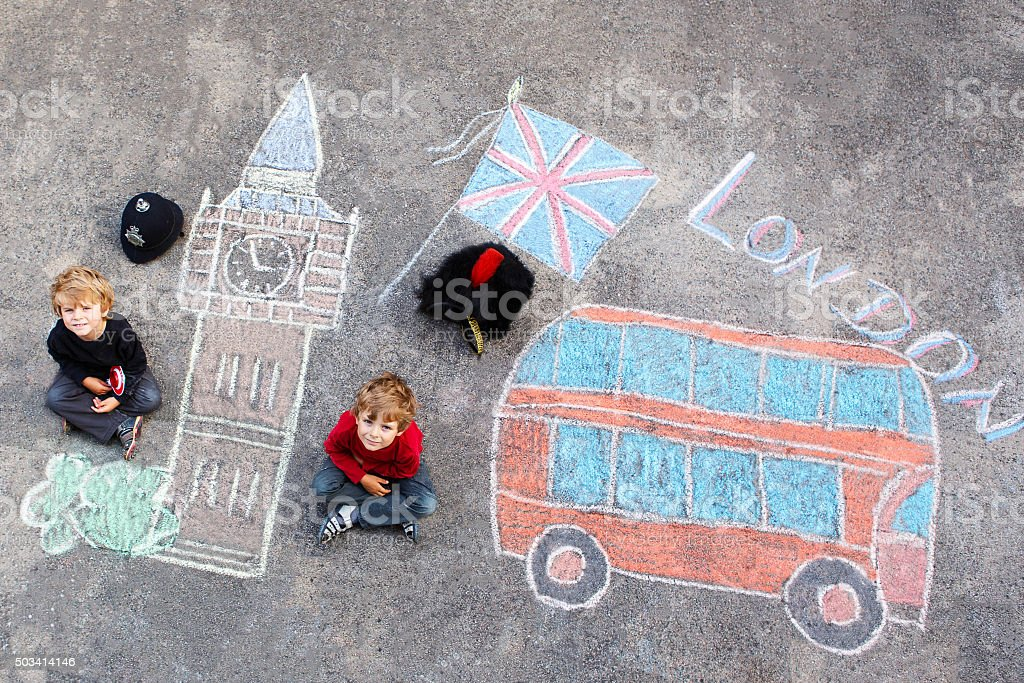 Two little kids with London picture drawing with chalks stock photo