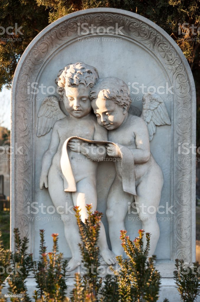 Two little marble angels reading a prayer on a gravestone stock photo