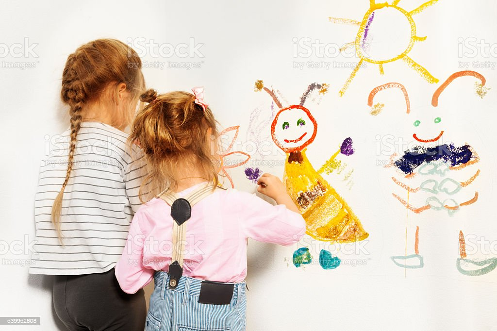 Two little painters drawing at the wall stock photo