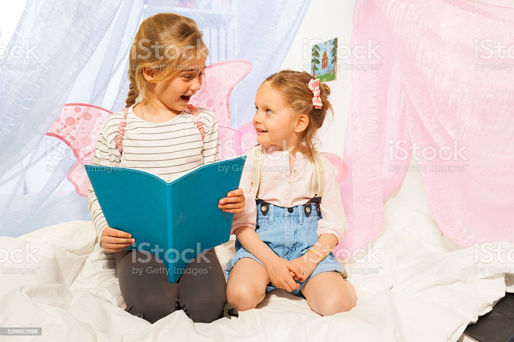 Two little pixies with wings reading bedtime story stock photo