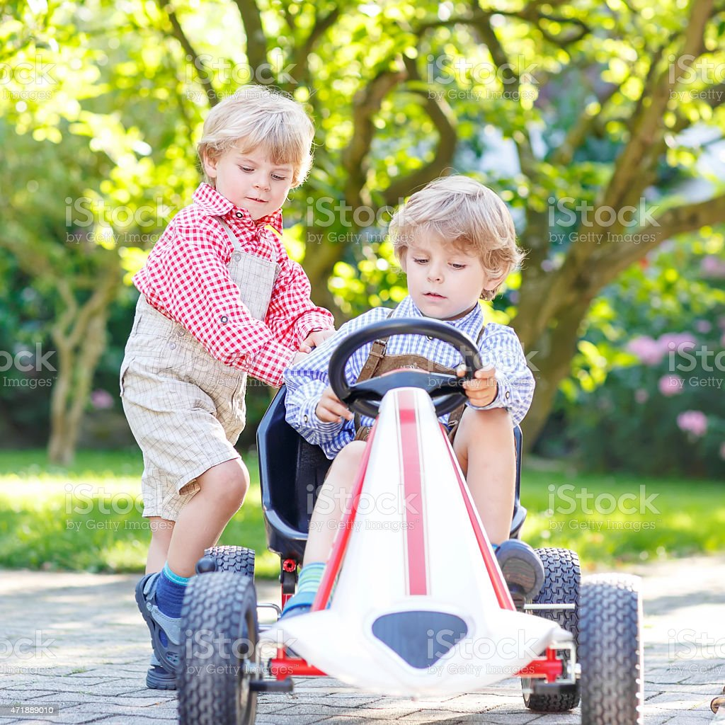 Two little sibling boys playing with pedal car stock photo