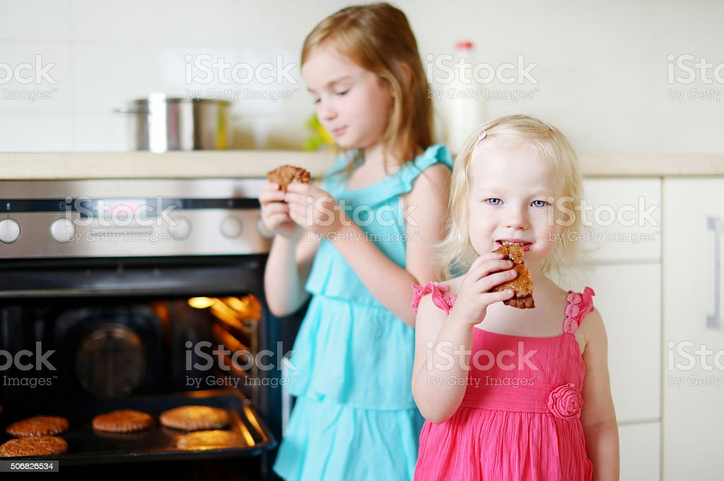 Two little sisters eating freshly baked cookies stock photo