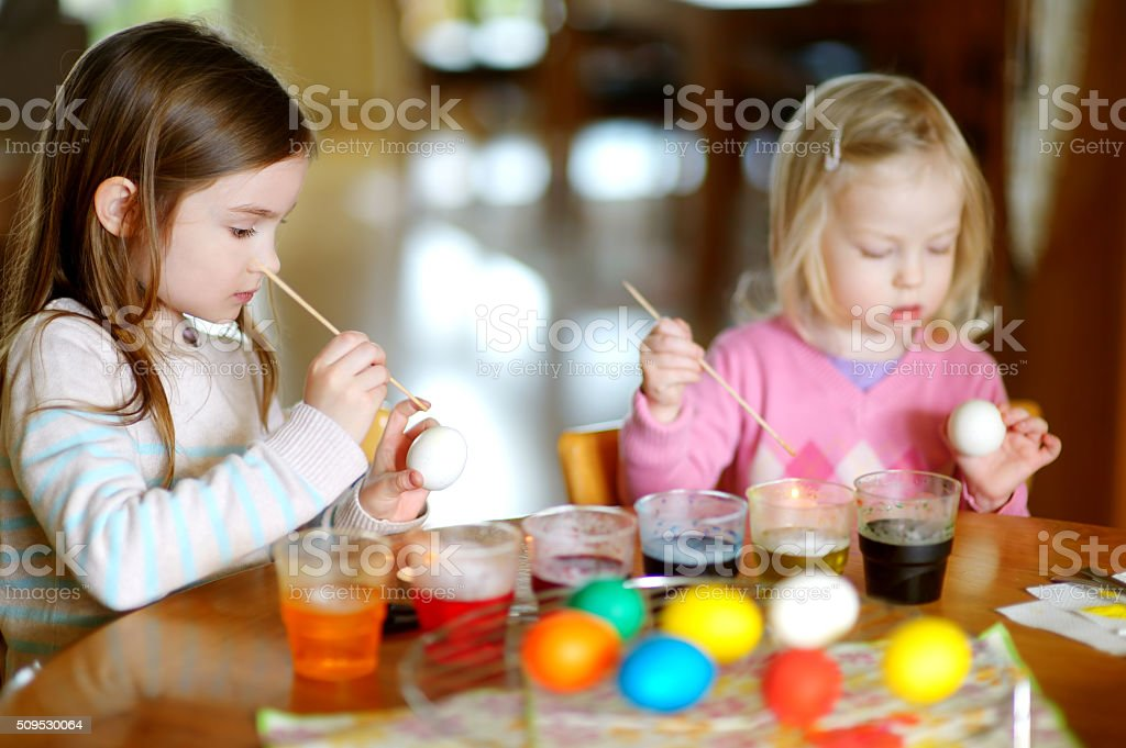 Two little sisters painting colorful Easter eggs stock photo