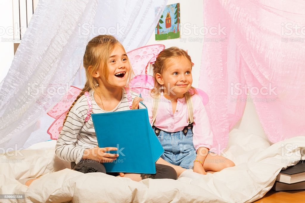 Two little smiling pixies reading the fairy-tale stock photo