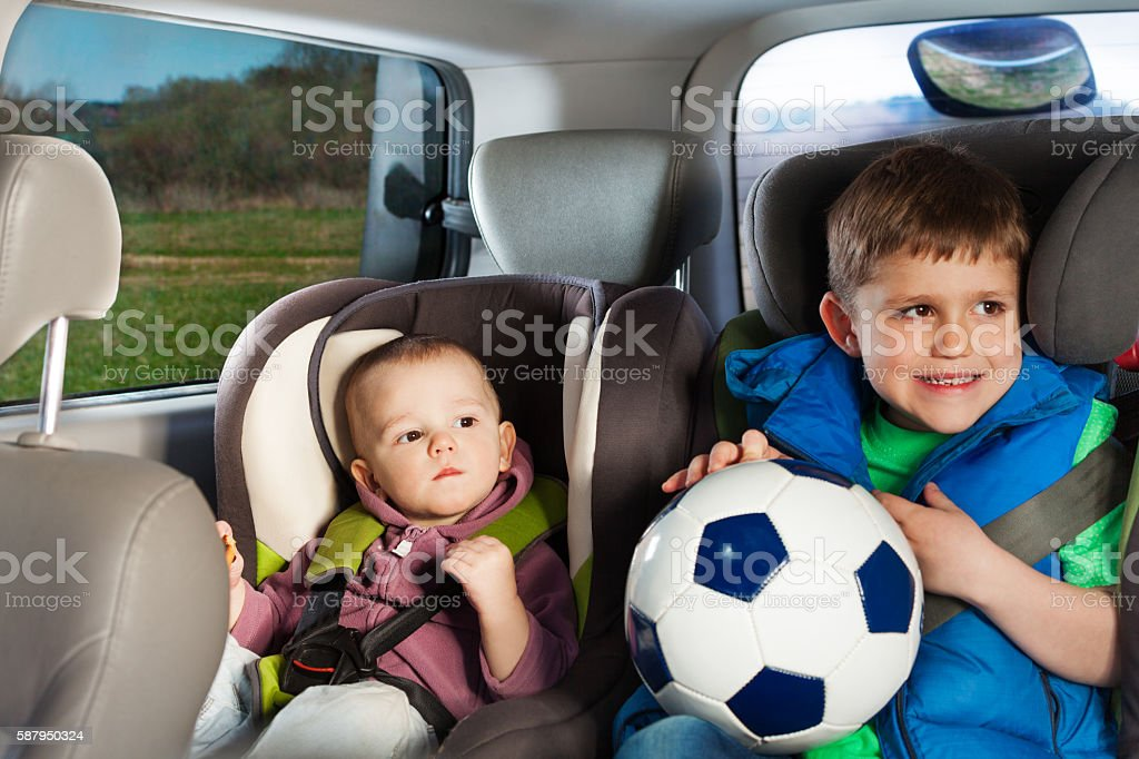 Two little travelers sitting in child safety seats stock photo