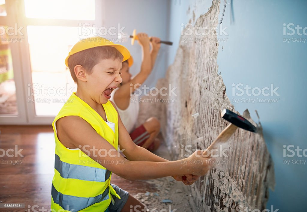 Two little workers tearing out plaster in their room stock photo