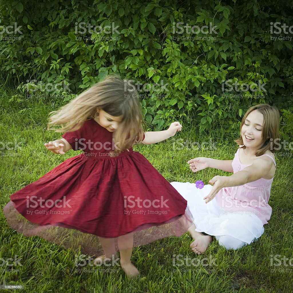 Two littles girls playing on the summer grass. stock photo