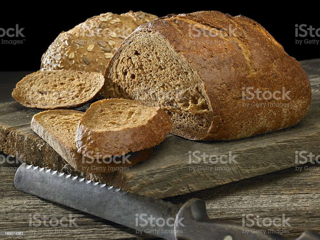 Two loaves of dark bread with old knife stock photo