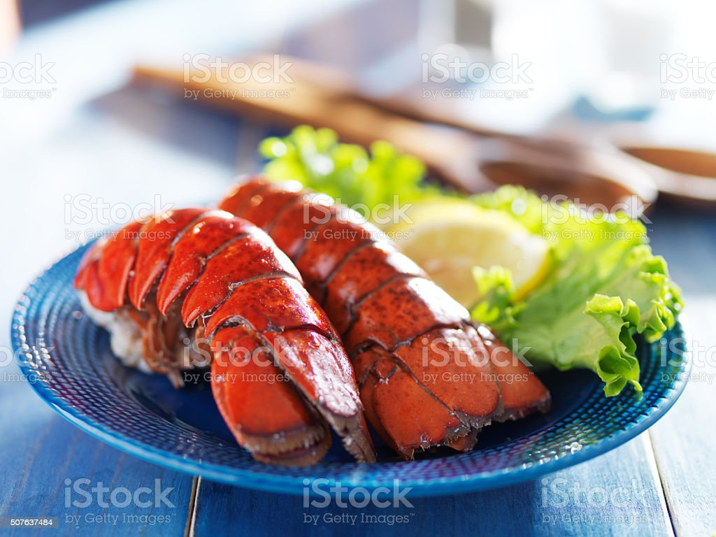 two lobster tails on blue plate with garnish for dinner stock photo