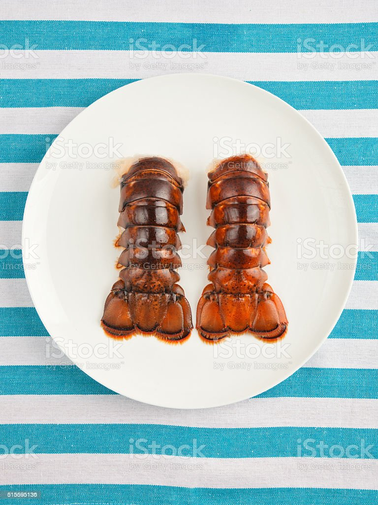 Two lobster tails on plate top view stock photo