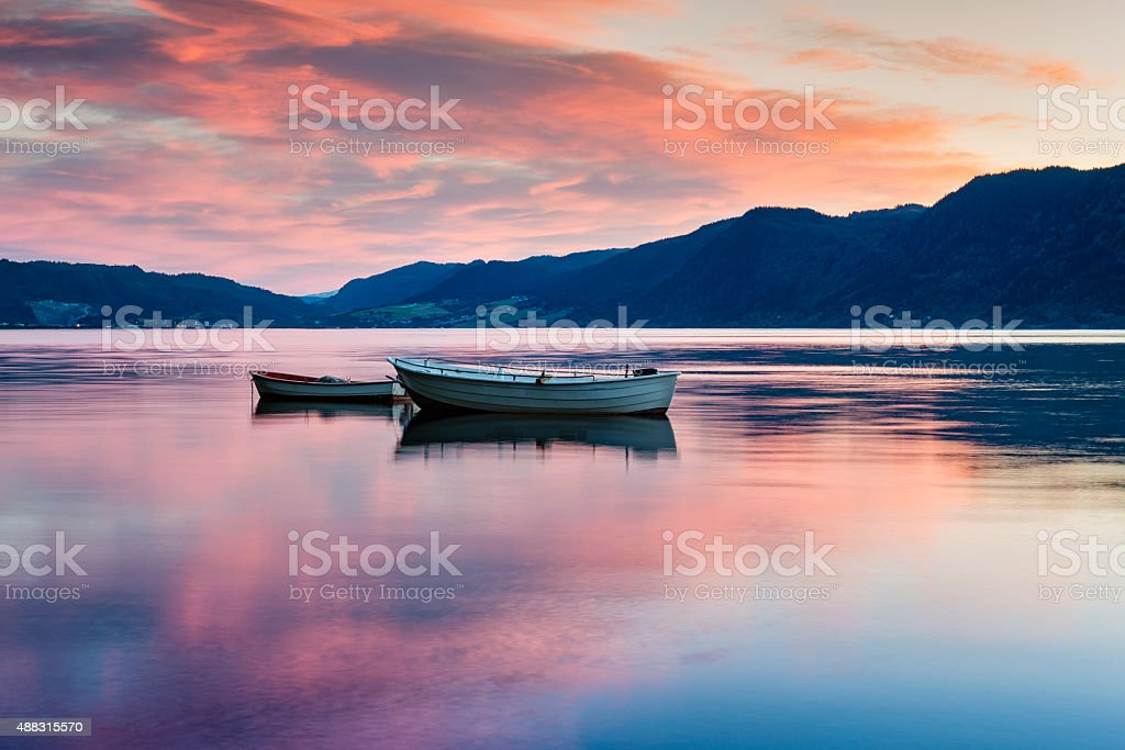 Two lonely boats on calm water of fjord. Norway. stock photo